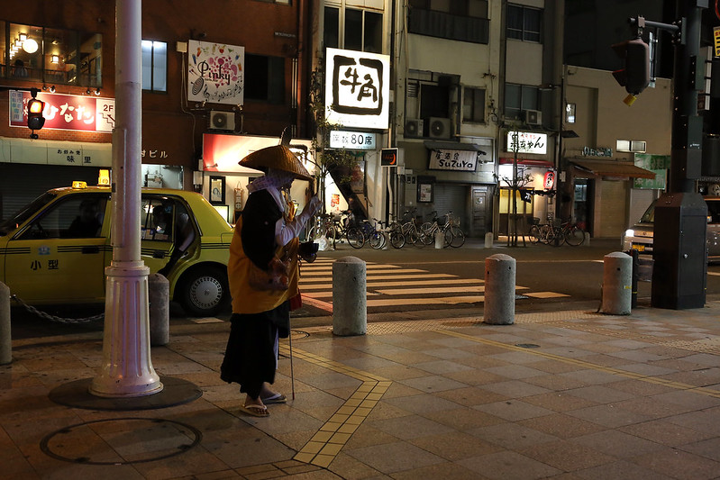 A mendicant monk on the night street in Tokushima