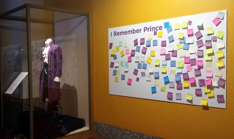 the suit in a protected box with an interpretive sign, and a large posterboard on the wall at the right with many Post-it notes