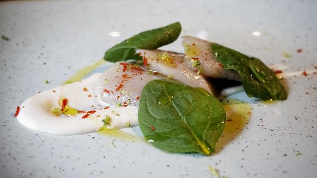 Arenque marinado con crema de yuzu, lima y ensalada de hojas verdes