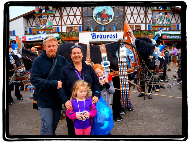 Children at Oktoberfest with their parents. There are horse behind them and a beer tent. Children love Oktoberfest!