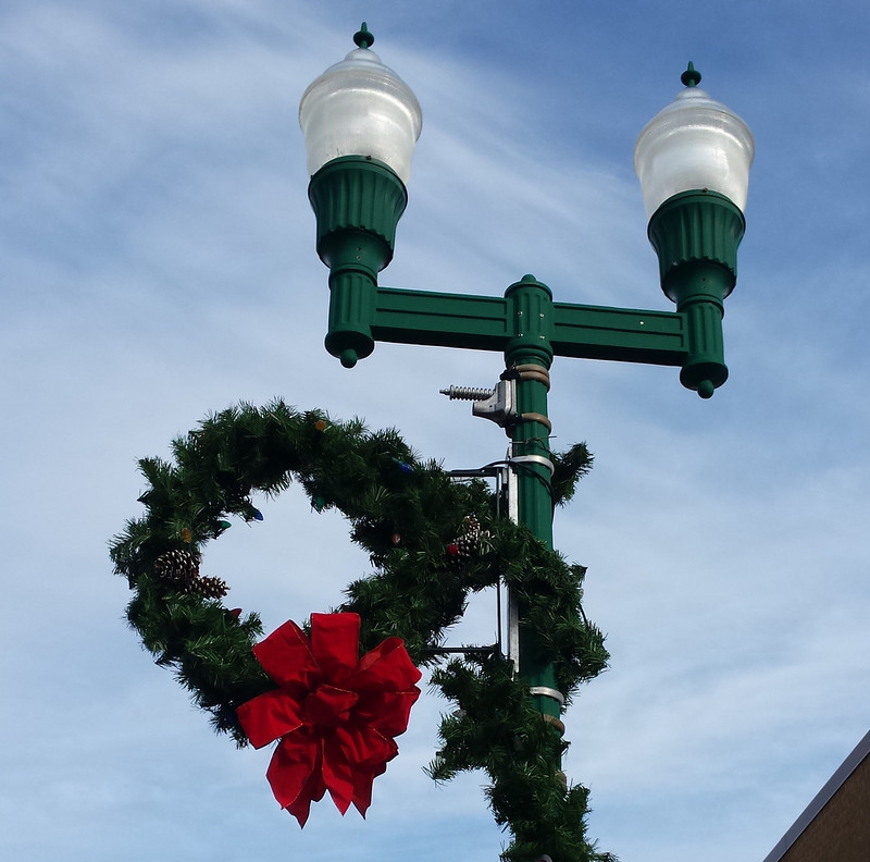 wreath on the left side of a lamppost with two lights