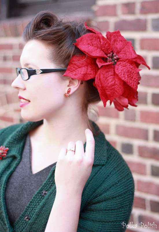 Retro Victory Roll hairstyle paired with an enormous fake poinsettia