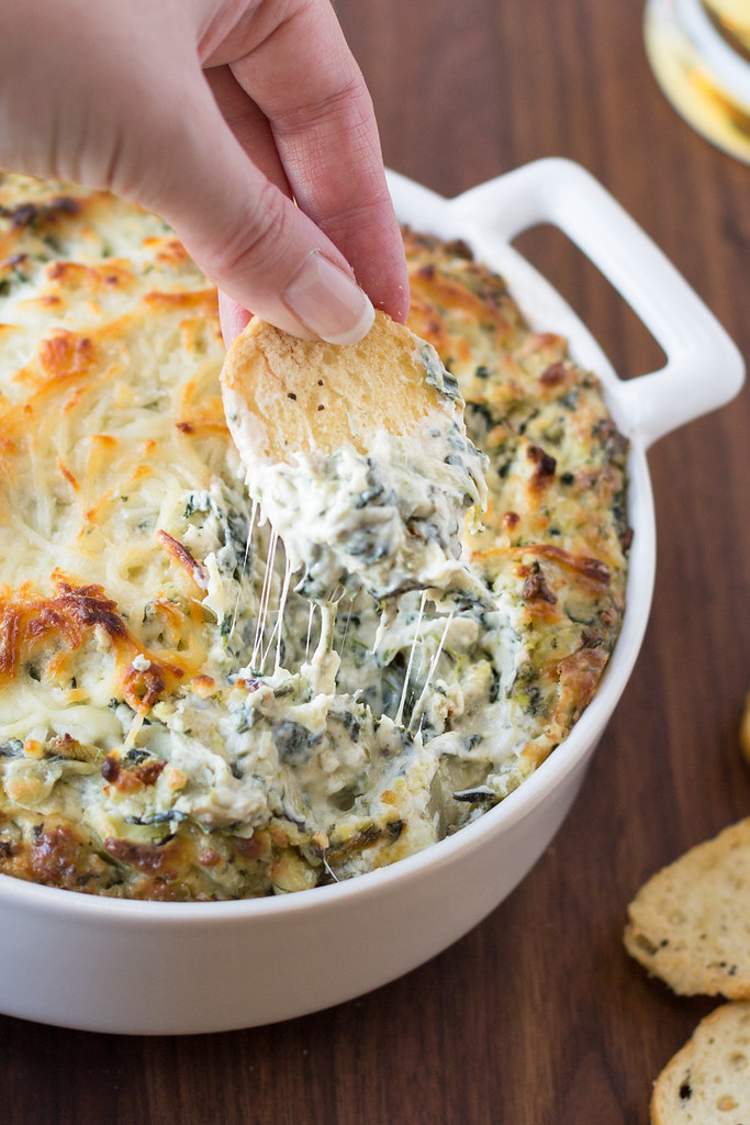 dipping into spinach and artichoke dip with melted cheese