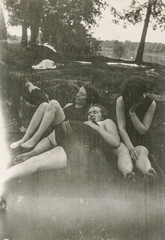 Women in swim suits sitting on the grass
