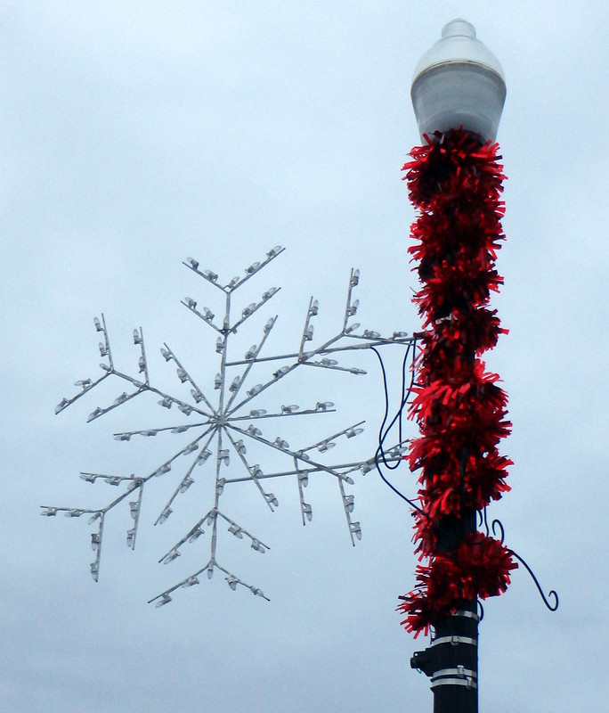 white snowflake decoration on a light pole wrapped with red tinsel