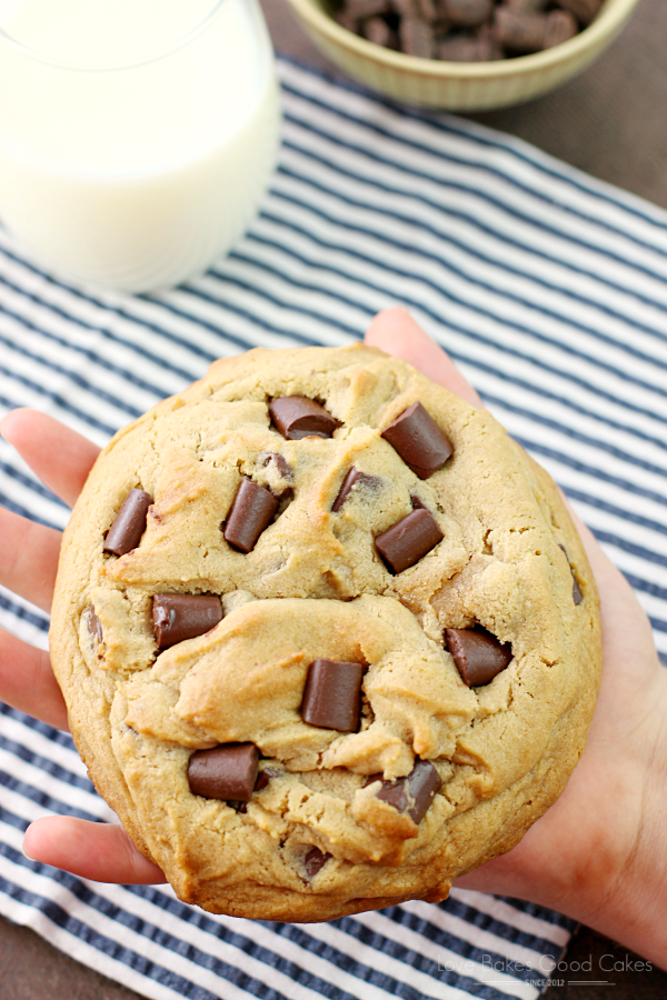 Giant Peanut Butter Cookie with Chocolate Chunks in someones hand with a glass of milk.