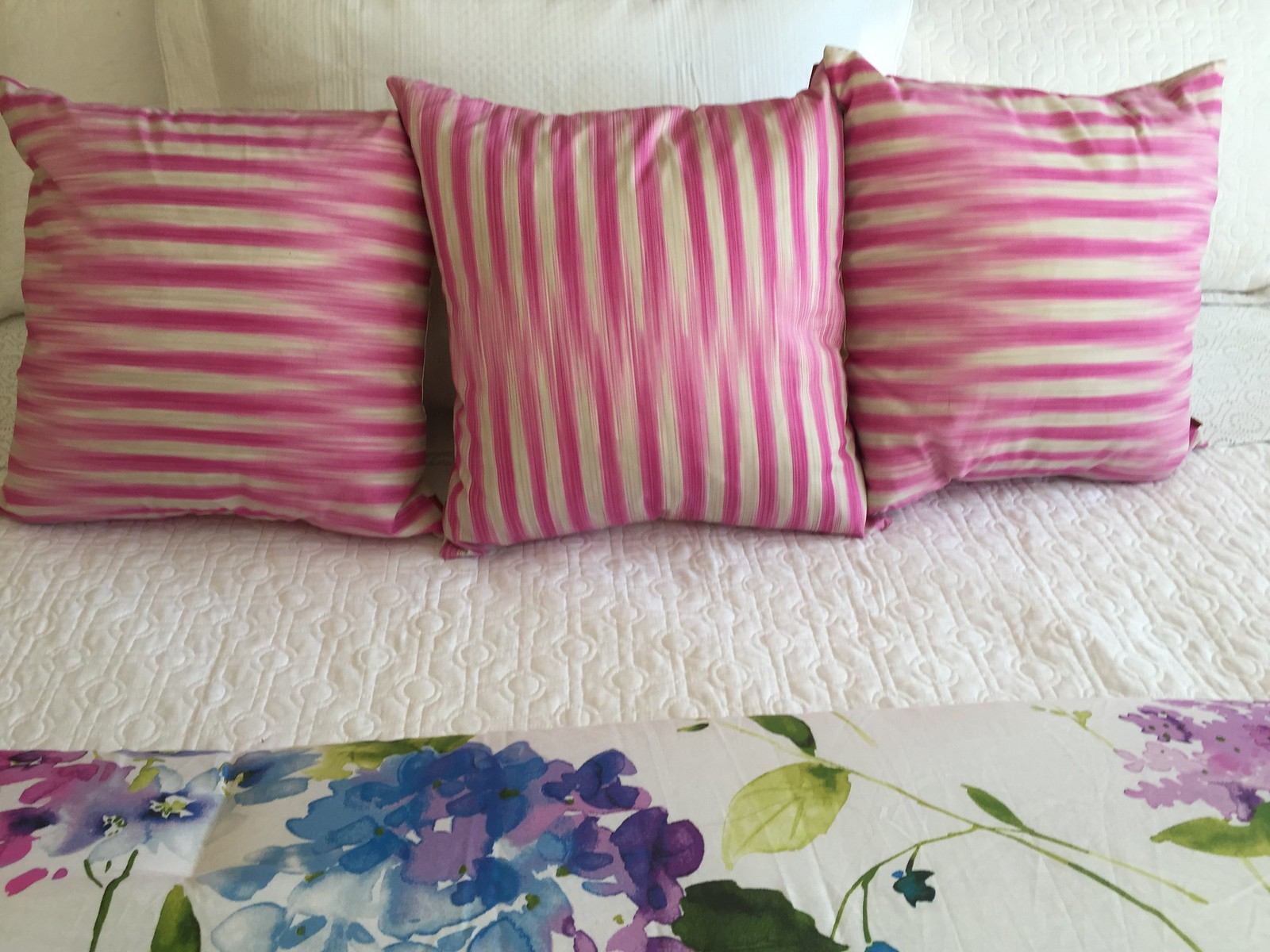 bright cushions with white coverlet and bright floral quilt