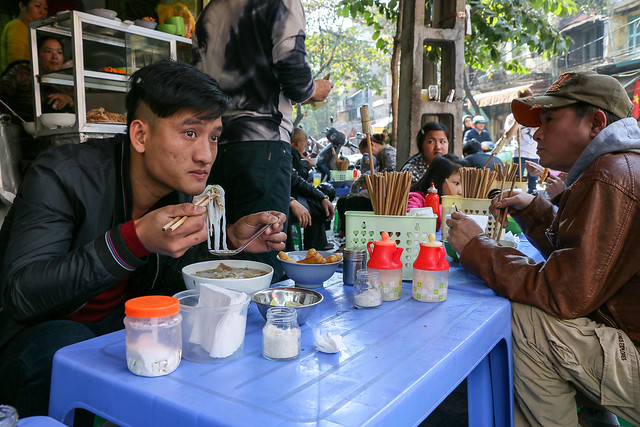 People eating Pho (Vietnam style noodles), Hanoi old city, Vietnam ハノイ旧市街、人気店でフォーを食べる人たち