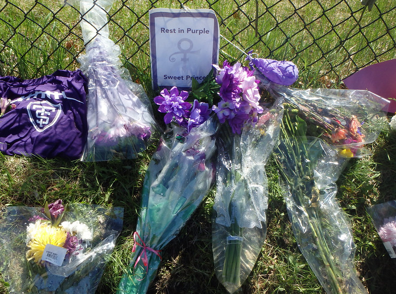 flower bouquets and a purple t-shirt near a paper sign that says Rest In Purple Sweet Prince