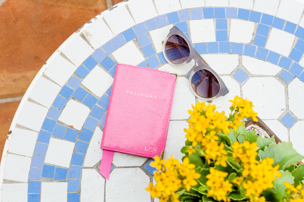 aspinal pink passport case and next sunglasses on mosaic table