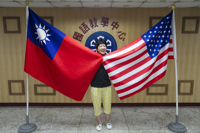 Posing with the Taiwan and US flags