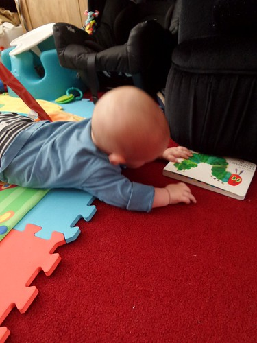 baby reaching for book, lower body on a brightly coloured play mat, upper body on carpet