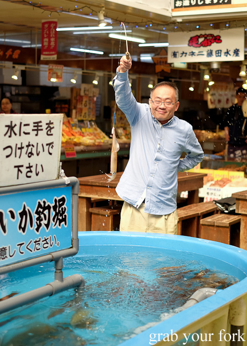 Successfully catching a live squid at Hakodate Morning Market, Japan