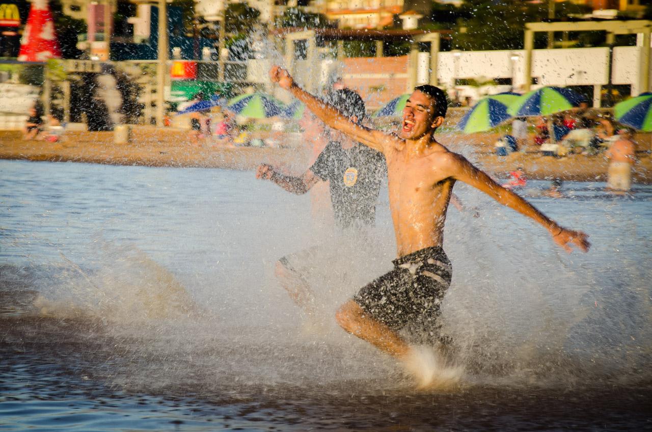 Jóvenes compiten en una carrera hasta las aguas del río Paraná, en la Playa San José de Encarnación. (Elton Núñez)