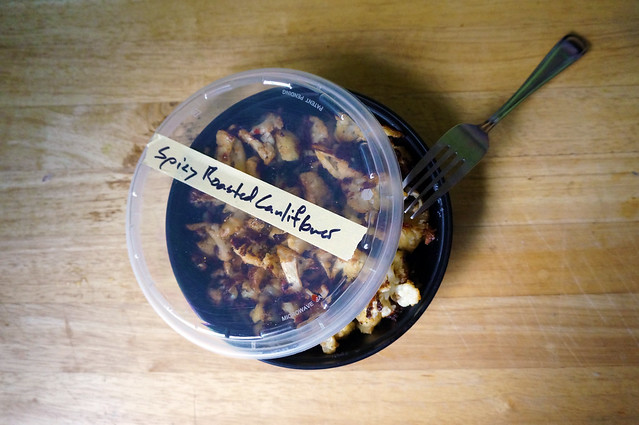 Spicy roasted cauliflower in a plastic tub, labeled with a handwritten piece of masking tape — you can eat it straight out of the fridge!