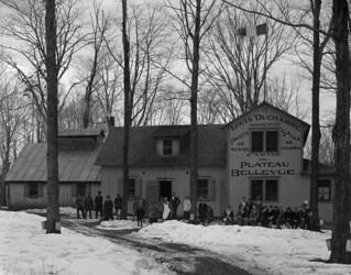Maple sugar bush—group of people in front of the Cabane du Plateau Bellevue, St. Hilaire, Québec / Érablière : groupe de personnes devant la Cabane du plateau Bellevue, à Saint Hilaire, au Québec