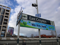 "Two long rectangular signs, the top one reading ""East Croydon / Fare Zone 5"" and the bottom one reading ""We live here / LV= / Liverpool Victoria"".  A multi-storey building under construction is behind to one side, and in the distance is Saffron Square, a purple-and-pink tower block."