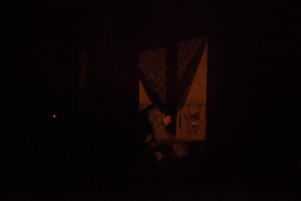 Az utcalámpa fénye befelé vet árnyékot, miközben Éva lázas gyermekének hőmérsékletét ellenőrzi. Éva egyik gyermeke napok óta lázas, a sarokban köhög, egy másik gyerek egy szál alsónadrágban ugrál a harmadik, aludni próbáló kétévesforma fiúcska feje fölött. Az ugráló kisfiú szeme furcsán villog nálunk lévő ledes lámpák fényében. Apjuk és nagyobb testvéreik az apa szüleinél vannak, ott tévéznek. | Fotó: Magócsi Márton