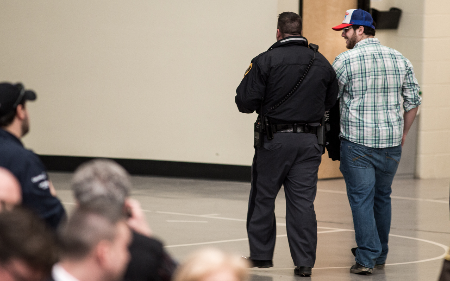 Michael Marmol is escorted from the Dedmon Center after disrupting the rally.
