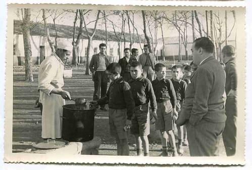 Colonia infantil de invierno en Villar del Pozo (Ciudad Real):  Niños haciendo cola esperando el rancho supervisados por el Sr. Gobernador Civil de Ciudad Real Don José María Moral y Pérez de Zayas