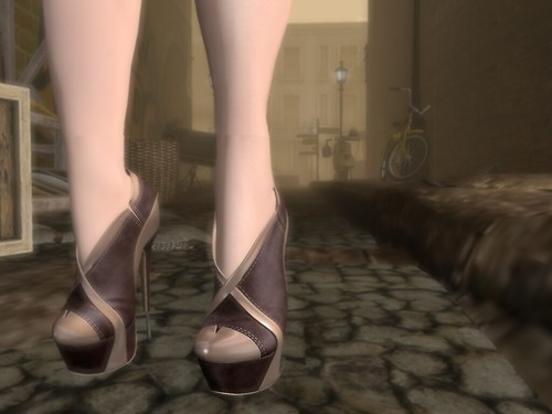Description: Close up of heels on a woman's feet in the foreground with a wide view of an alleyway beyond her ankles.