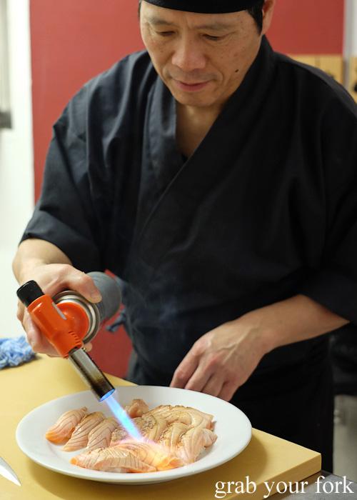 Chef Shinji Matsui blowtorching salmon belly at Sashimi Shinsengumi, Crows Nest
