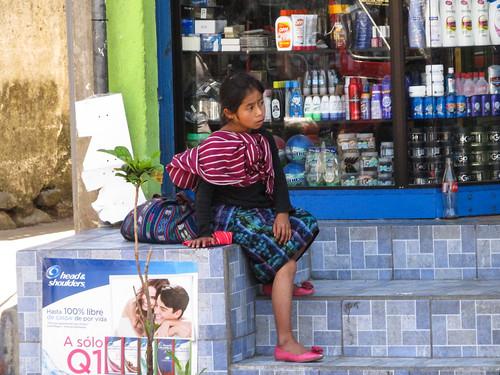 Panajachel: une petite fille en habit traditionnel. Mais que cache-t-elle derrière son dos?