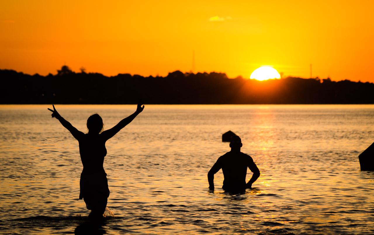 Bañistas despiden al sol durante el atardecer en las aguas del río Paraná, en la concurrida Playa San José de Encarnación. (Elton Núñez)
