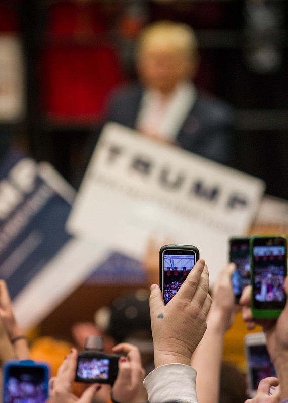Rally attendees hold their phones up to capture Trump as he arrives at the podium.