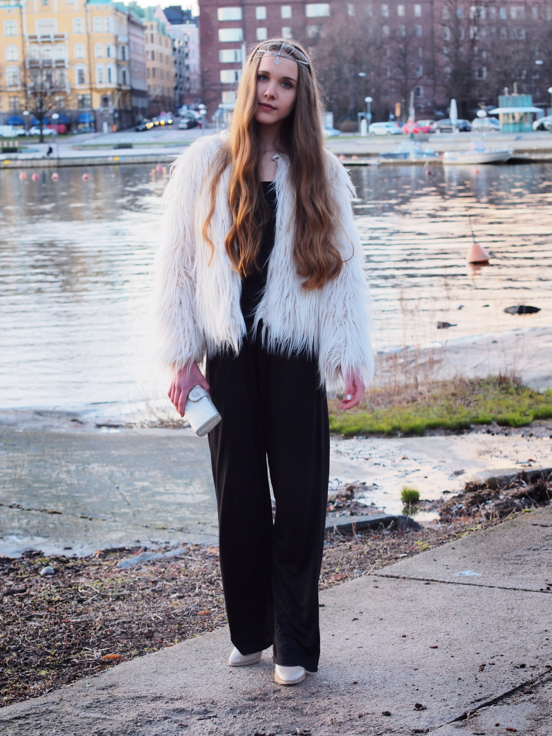 Black jumpsuit, white faux fur coat, silver headpiece and clutch, nude heels