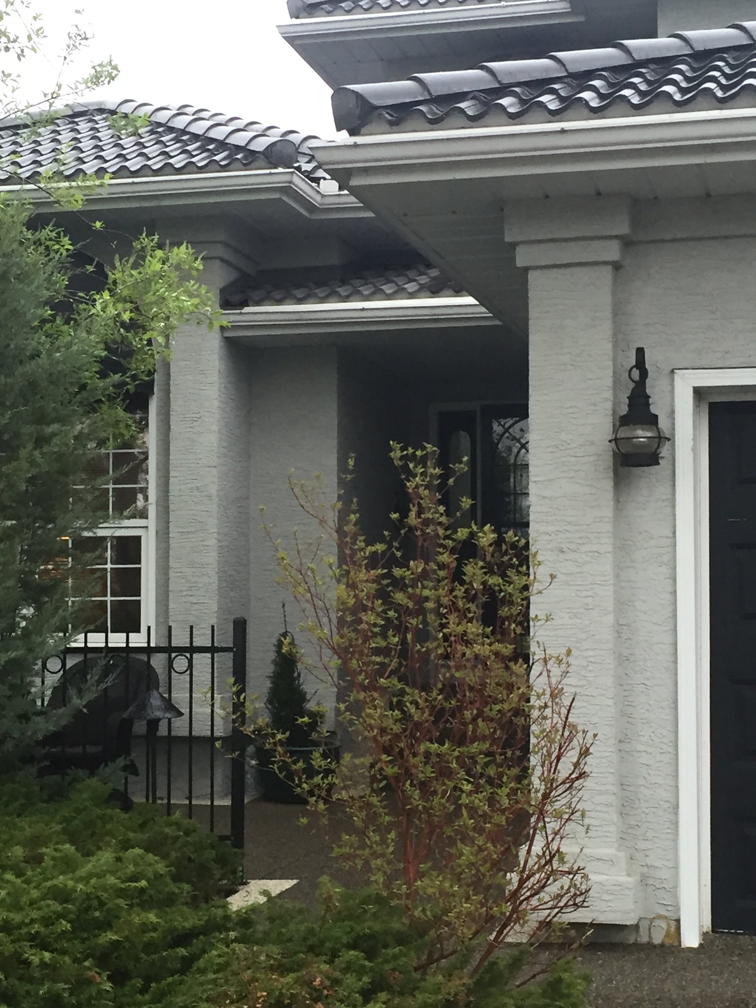 exterior close up of stucco home painted grey with black accents