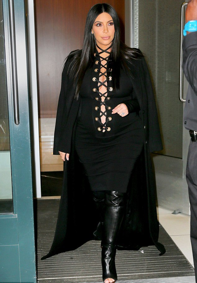 Givenchy lace up jersey dress thigh high leather boots and a black long coat over her shoulder to finish off her look