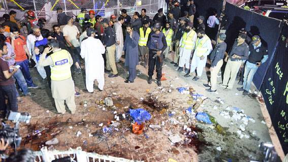 Pakistani rescuers and officials gather at a bomb blast site in Lahore on Sunday.