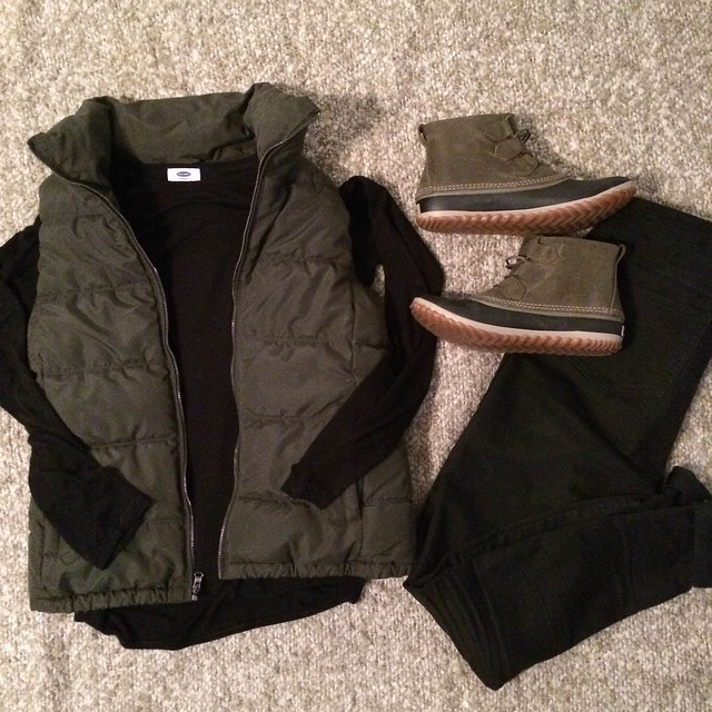 olive vest + black top + sorel boots + black skinny jeans