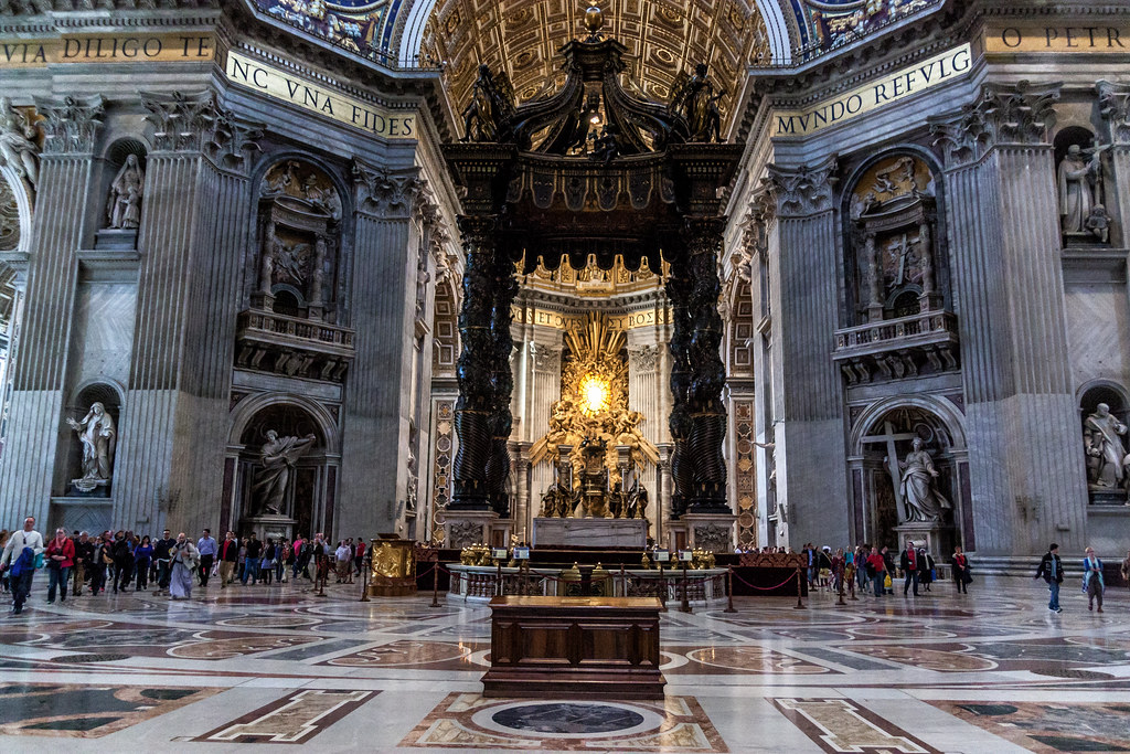 "The papal altar in the middle of the church is surmounted by the famous gilded bronze baldachin, designed by a youthful Bernini between 1624 and 1632. It stands 29 metres high and was commissioned by Pope Urban VIII Barberini (1623-1644) to fill the ""empty"" space below the dome and create an upward movement."