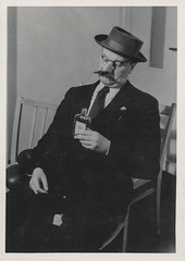 Man with a fake moustache drinking at a party