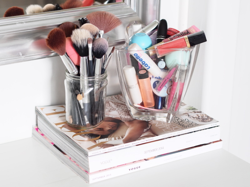 Make up brushes and lip products on top of a few issues of Vogue