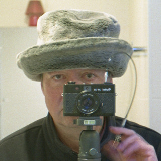 reflected self-portrait with Rollei XF 35 camera and fur hat (square crop)