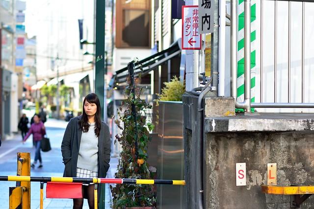 踏切で線路を挟んで女性を撮影したポートレート写真