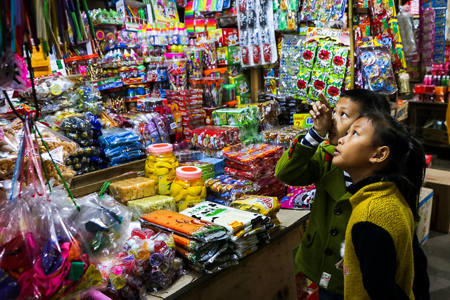 Children in the Talat Phosi market, Luang Prabang, Laos ルアンパバーン、市場でオヤツを見てる子どもたち