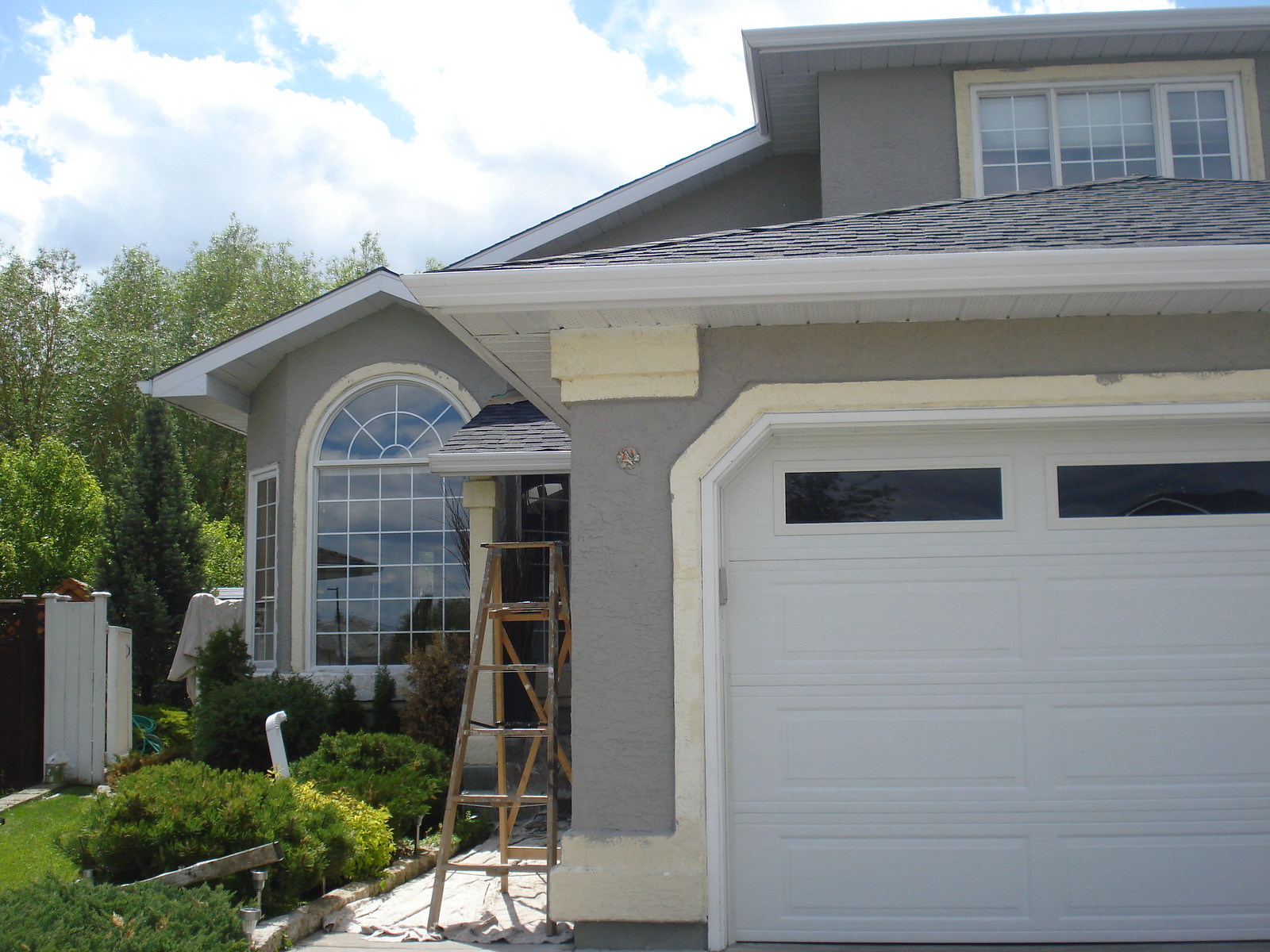 Exterior of a yellow home getting painted to Benjamin Moore Rockport Grey