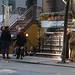 A noisy crowd taking a smoke break on 51st Street outside a South African restaurant.