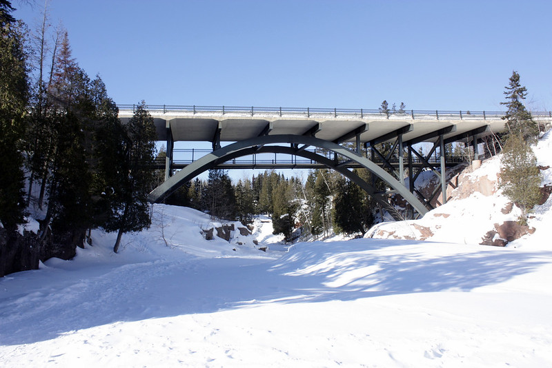 Steel arch bridge over a snow-covered river