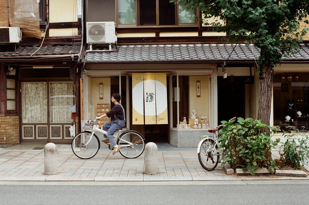 寺町通 京都 Kyoto / Kodak ColorPlus / Nikon FM2 2015/09/27 整理照片的時候發現我那時候在寺町通也拍了滿多街上騎腳踏車的路人,這裡街道不寬,兩旁都有看起來好像是歷史很久的店家,店家門面都很有特色。  我想起來了,那時候拍照有規定自己畫面中一定要有當地人入鏡,因為之前拍太多空無一人的畫面,畫面太過空寂。  Nikon FM2 Nikon AI Nikkor 50mm f/1.4S Kodak ColorPlus ISO200 0985-0033 Photo by Toomore
