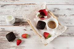 Chocolate muffins, coffee, strawberries, a vase of…