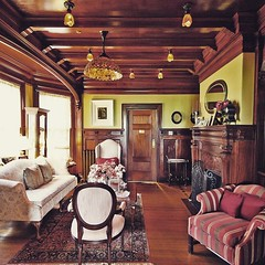 One of the most spectacular cherry wood clad formal living rooms with original Tiffany lighting! Greenville Inn #moosehead #maine #innsforsale #innkeeping