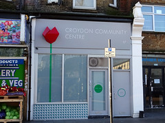 "An end-of-terrace shopfront with another building recessed behind to the side.  The shopfront is painted in grey and has a 3-D stylised red rose to the left of the frontage sign, with a painted green stem running down from there over the opaque shop window and down to the riser.  Next to the rose, the sign reads ""Croydon Community Centre""."
