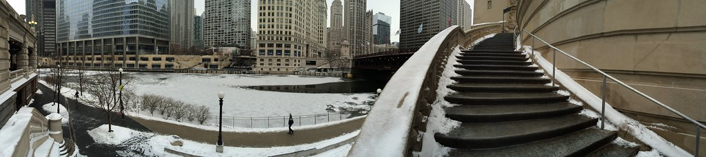 Panoramic of frozen Chicago River and snow capped staircase of Michigan Avenue bridge