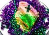 Mardi Gras beads surround a slice of King Cake in Mobile Alabama
