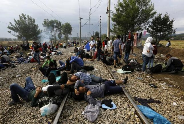 Syrian refugee prays on a rail track at the Greek-Macedonian border, near the village of Idomeni